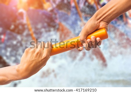 hands passing a relay baton on rowing team background and color tone effect. - stock photo