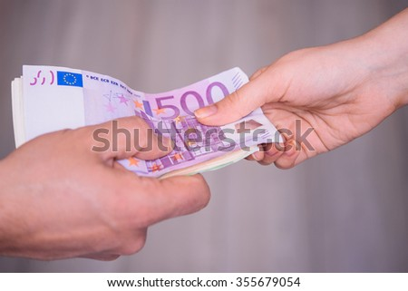 Hands passing money, Euro currency (EUR)