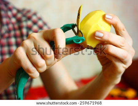 hands peeling potato with vegetable cutter slicer slicing  machine - stock photo