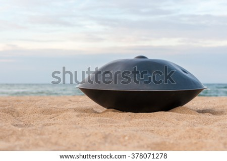 Hands percussion instrument named the Hang or handpan with sea On Background. the hang is a traditional ethnic drum musical instrument. - stock photo