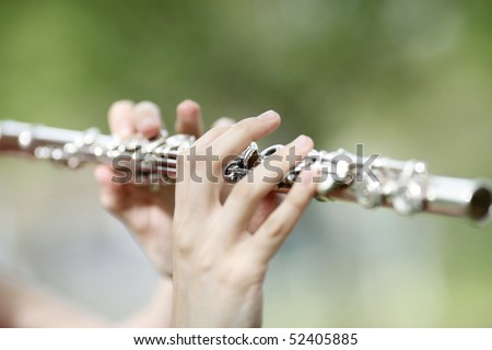 Hands playing classic flute in nature in background. Shallow DOF