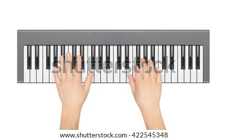 Hands playing electronic piano on a white background. View from the top.
