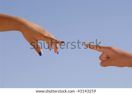 Hands pointing to another over a blue sky