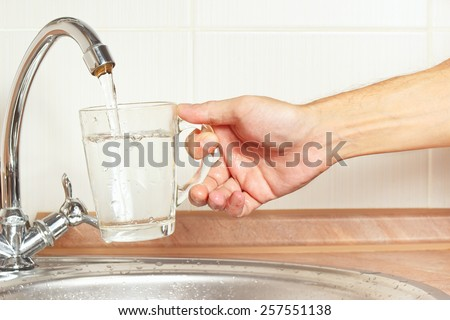 Hands pour fresh water into the glass under the tap in the kitchen - stock photo