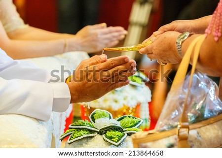 hands pouring blessing water into groom's bands, Thai wedding ceremony