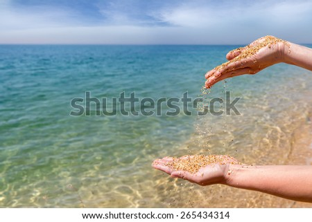 Hands pouring coral sand on the sea background - stock photo