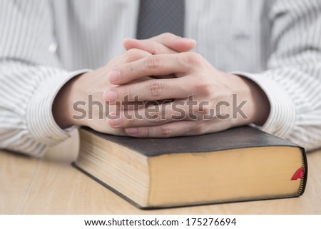 hands praying with bible on table - stock photo