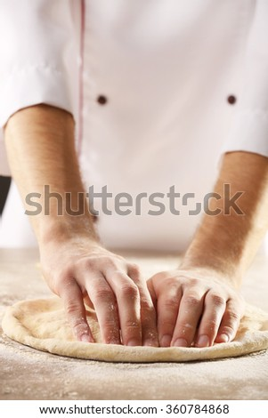 Hands preparing dough basis for pizza on the wooden table, close-up