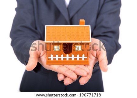 Hands presenting a small model of a house - stock photo