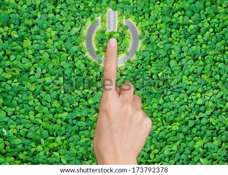 hands pressing shut Down button on green leaf background - stock photo