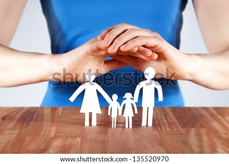 hands protecting a white paper chain family - stock photo
