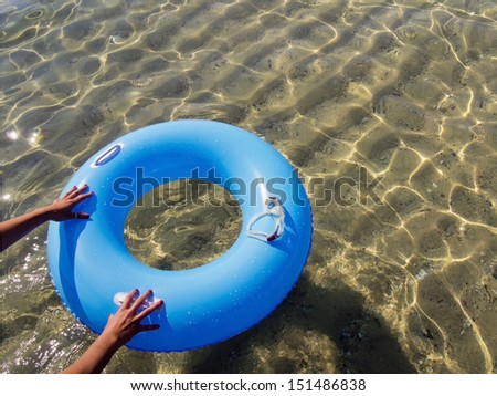 hands pushing a blue donut inflatable in the sea - stock photo