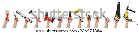 Hands raised holding different tools - stock photo