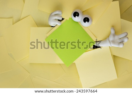 Hands reach out and eyes peer out from under several bright yellow sticky notes and a green one as well. - stock photo