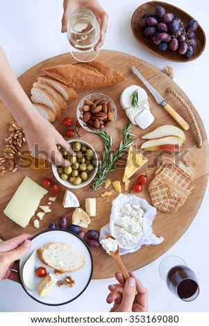 Hands reaching for food on a well spread cheese platter, party snack appetizer served with wine
