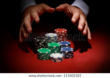 Hands reaching for Poker chips on red background