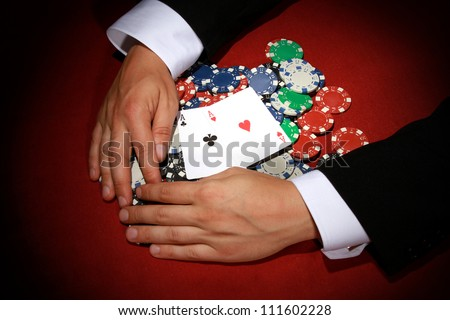 Hands reaching for Poker chips on red background - stock photo