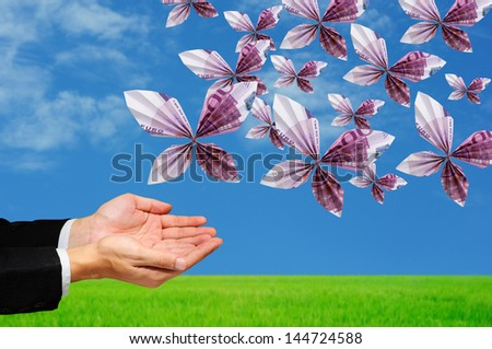 hands releasing origami butterfly made from 500 Euro banknotes - stock photo
