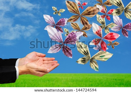hands releasing origami butterfly made from mix banknotes - stock photo