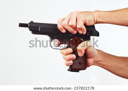 Hands reload gun on a white background - stock photo