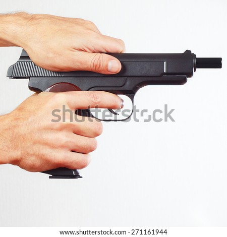 Hands reload handgun on a white background - stock photo