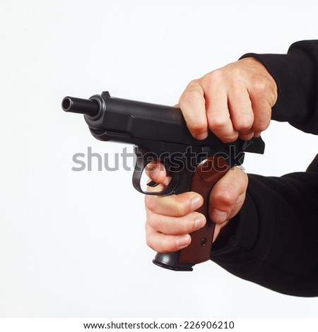 Hands reload semi-automatic pistol on a white background - stock photo