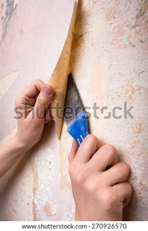 hands removing old wallpaper from wall - stock photo