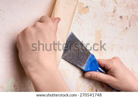 hands removing wallpaper from wall  - stock photo