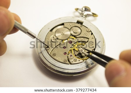 hands repair an old watch with white background - stock photo