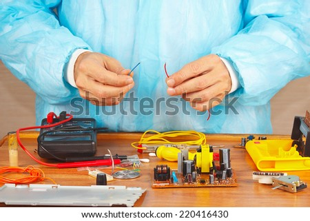 Hands repairman servicing electronic devices in the service workshop - stock photo