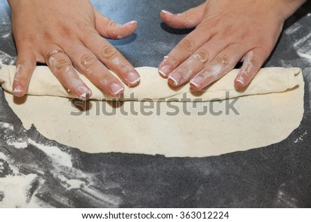 Hands rolling thin dough with filling