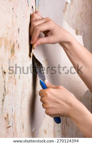 hands scraping off old wallpaper - stock photo