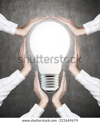 Hands secure a light bulb. Concrete background. - stock photo