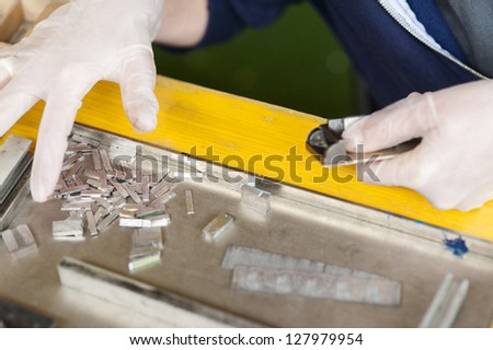 hands selecting letters for old printing press - stock photo