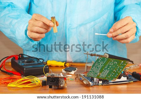 Hands serviceman electronic devices in the service workshop - stock photo