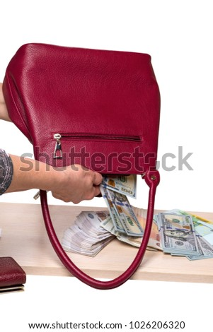 Hands shake out paper money from a shopping bag on a table