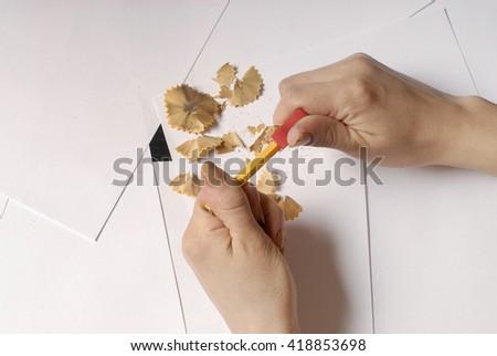 hands sharpen a pencil - stock photo
