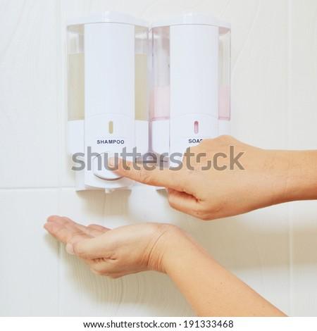 Hands shot up finger presses shampoo bottle pump shampoo. - stock photo