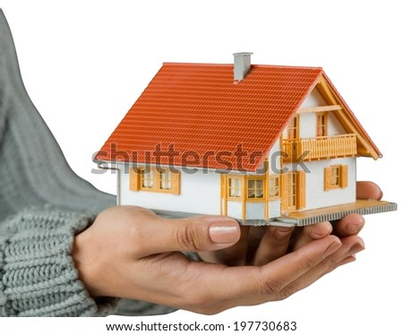 Hands showing a miniature model home on white background