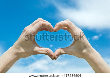 Hands showing heart against the sky