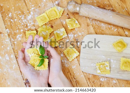 Hands showing ravioli pasta with basil on a wooden table