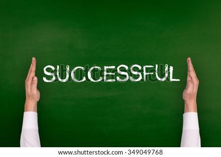 Hands Showing SUCCESSFUL on Blackboard - stock photo