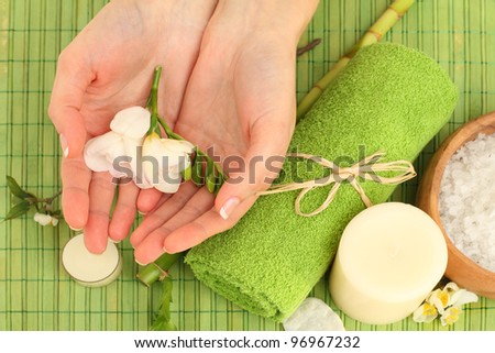 Hands spa - green background with flowers and bamboo - stock photo