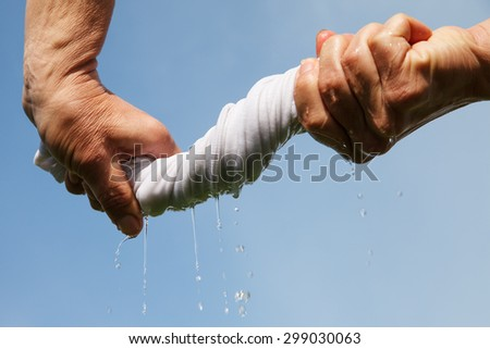 Hands squeeze wet fabric against blue sky.