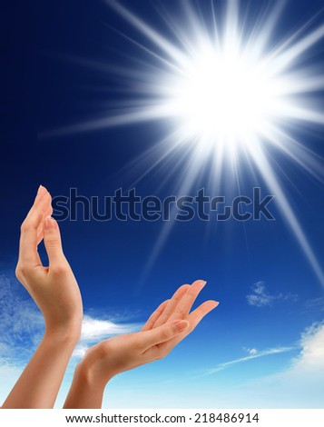 Hands, sun and blue sky with copyspace showing freedom or solar power concept - stock photo