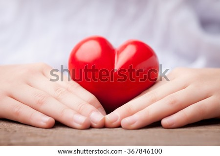 hands surrounding a heart as safety concept - stock photo