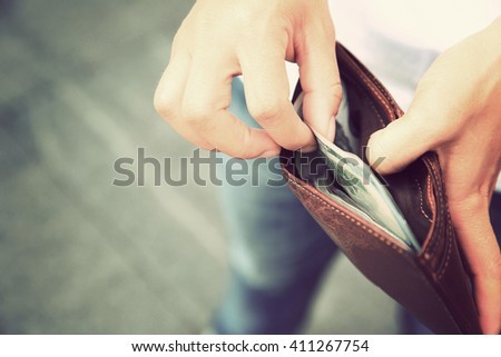 Hands taking out money from wallet on street - stock photo