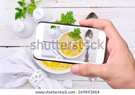Hands taking photo chicken noodle soup with smartphone. - stock photo