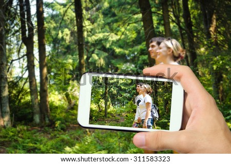 Hands taking photo young girl and man  in mountain with smartphone.