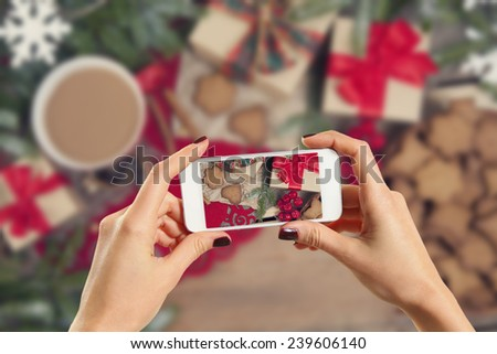 Hands taking picture of gingerbread cookies - stock photo